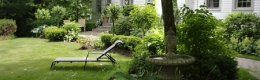 In the front garden under a large linden trickles a fountain accompanied by lounge chair